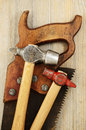 Two hammer and old saw on wooden background Stock Image