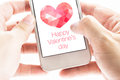 Two hand holding smartphone with pink polygon heart shape and ha happy valentine s day on screen love concept Royalty Free Stock Photo