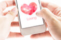 Two hand holding smartphone with pink polygon heart shape and lo loving word on screen love concept Royalty Free Stock Images