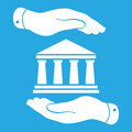 Two hands with badge with white bank icon on a blue background - Royalty Free Stock Photo