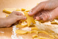 Two hands, child and women, making cookies from the dough Royalty Free Stock Photo