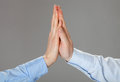 Two hands giving high fives on grey background Stock Images