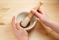 Two hands holding a pestle and mortar with whole coriander seeds Royalty Free Stock Photo