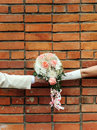 Two hands holding wedding bouquet against a brick wall. Stock Images