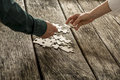 Two hands male and female matching two puzzle pieces over a pi pile of other lying on textured rustic wooden desk conceptual Royalty Free Stock Photography