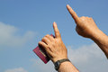 Two hands and a passport saying travel fingers pointing up to the blue sky in one hand fly or Stock Photography