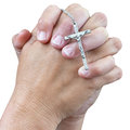 Two hands praying with a small silver crucifix Royalty Free Stock Photo