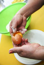 Two hands separating eggwhite from yolk over green Royalty Free Stock Photo