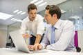 Two handsome businessmen working together on a laptop in the off males computer pc desk planning work tie Stock Image
