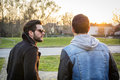 Two handsome young men, friends, in a park Royalty Free Stock Photo
