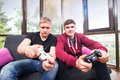 Two handsome young men playing video games while sitting on sofa Royalty Free Stock Photo