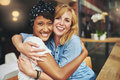 Two happy affectionate young woman hugging women each other in a close embrace while laughing and smiling multiracial female Royalty Free Stock Image