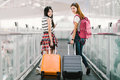 Two happy Asian girls traveling abroad together, carrying suitcase luggage in airport. Air travel or holiday vacation concept Royalty Free Stock Photo
