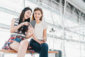 stock image of  Asian girls using smartphone checking flight or online check-in at airport together, with luggage. Air travel, summer holiday