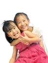 Two happy asian little sisters hugging siblings love together isolated on white background Royalty Free Stock Photos