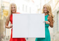 Two happy blonde women with blank white board summer holidays travel tourism and advertisement concept in the city Royalty Free Stock Photos