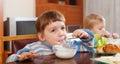 Two happy children eating dairy breakfast