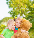 Two happy children enjoying big brown soft bear outdoors brother and sister hugging having fun on spring time love and happiness Stock Image