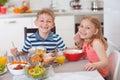Two happy children having breakfast in kitchen Royalty Free Stock Photo