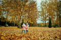 Two happy children playing in autumn clothes in the park. Royalty Free Stock Photo