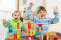 Two happy children playing with blocks in home