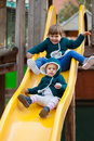 Two happy children on slide at playground in autumn Stock Photos