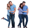Two happy couples of young casual people standing embraced on white background Stock Photos