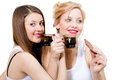 Two happy female friends drink tea and eating chocolate bar isolated on white background Stock Photo