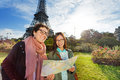 Two happy friends sightseeing Paris with map Royalty Free Stock Photo
