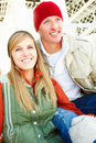 Two happy friends in winter wear sitting together Stock Photo