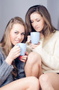 Two happy girlfriends drinking tea together smiling looking at camera young women Royalty Free Stock Images