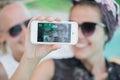 Two happy girlfriends in sunglasses doing selfie