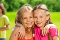 Two happy girls hugging close up of standing in the park together and with big smile on faces Royalty Free Stock Photography