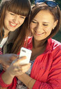 Two happy girls with mobile phone Royalty Free Stock Photos