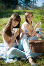 Two happy girls on picnic drinking tea Stock Photo