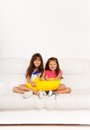 Two happy girls with pillows preschool asian and caucasian calm and relaxed years old sitting pillow on the white leather coach in Royalty Free Stock Image