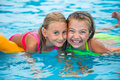 Two happy girls playing in the pool on a sunny day. Cute little girls enjoying holiday vacation Royalty Free Stock Photo