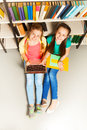 Two happy girls portrait from above sit on floor who look up and in library Stock Image