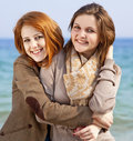 Two happy girls at spring beach. Royalty Free Stock Images