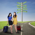 Two happy girls with suitcases standing on the road Stock Image