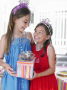 Two happy girls in tiaras holding present portrait of Royalty Free Stock Image