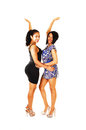 Two happy girls very young women in dresses and high heels standing for white background lifting there arms Stock Photography