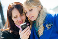 Two happy girls watching something in mobile phone Royalty Free Stock Photo