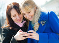 Two happy girls watching something in mobile phone Royalty Free Stock Images