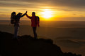 Two happy hikers climb in the mountains of the sunset Stock Photo