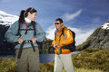 Two happy hikers on mountain landscape young male and female with backpacks smiling Stock Image