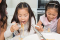 Two happy kids enjoying spaghetti lunch in kitchen closeup of the at home Stock Image
