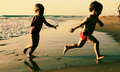 Two happy kids playing on the beach at sunset Stock Photography