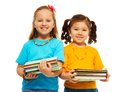 Two happy little girls asian caucasian black light haired stack books standing isolated white Stock Image