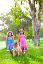 Two happy little girls and a golden retriever Stock Image